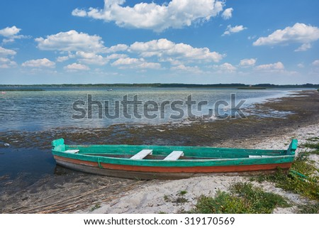 Sunny day on the lake, wooden fishing boat, beach on the lake, reeds - stock photo