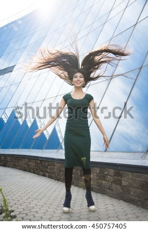 sunny day with sun rays. japanese jumping student girl with flying long brunette hair. Idea, symbol, concept of liberty, freedom, growth and happiness