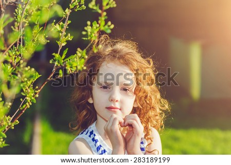 Sunny girl folded her hands a heart shaped, background toning for instagram filter. - stock photo