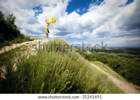 sunny girl is jumping with multicolored balloons - stock photo