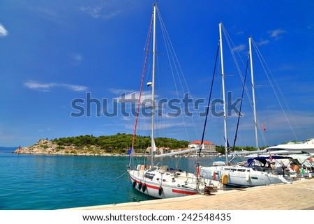 Sunny harbor and white sail boats by the pier, Makarska, Croatia - stock photo