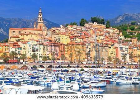 Sunny harbor with historical town of Menton in the background, French Riviera, France - stock photo