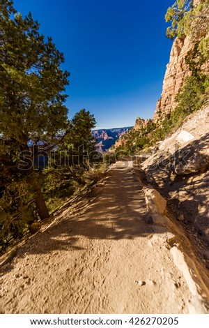 Sunny hiker path in the rocky Grand Canyon with clear blue sky - stock photo