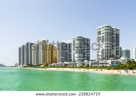 SUNNY ISLES BEACH, USA - AUG 17, 2014: people enjoy Jade beach and Jade Ocean condominiums. Jade Beach and Ocean were completed in 2009 with a elevation of 549 feet. - stock photo