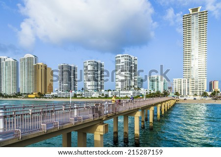 SUNNY ISLES BEACH, USA - AUG 17, 2014: people walk at the pier in Sunny Isles Beach, USA. In 1936, Milwaukee malt magnate Kurtis built the Sunny Isles pier. - stock photo