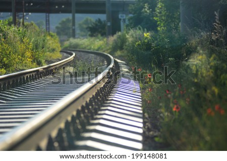 Sunny landscape with railroad tracks - stock photo