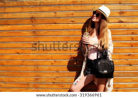Sunny lifestyle fashion portrait of young stylish hipster woman walking on the street, wearing trendy outfit, hat, kimono, drinking tasty smoothie, travel with backpack. Wood background - stock photo