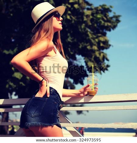 Sunny lifestyle fashion portrait of young stylish hipster woman walking on the street, wearing trendy outfit, hat, drinking tasty smoothie, travel with backpack.  - stock photo