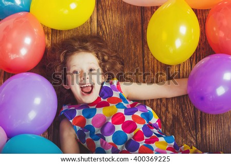 Sunny little girl in birthday party lying on wooden floor with rainbow balloons. Happy childhood concept.