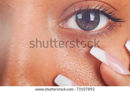 sunny macro photo of a mulatto female eye and fingers