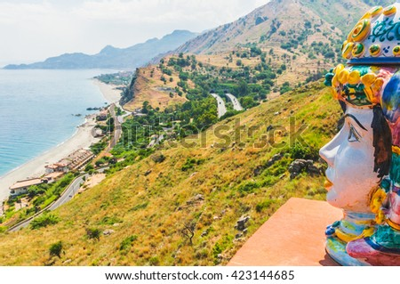 Sunny mediterranean small medieval town with painted face figurines amazing view with the azure blue sea panorama in the background, Taormina, Sicily, Italy - stock photo