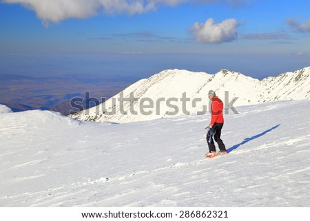Sunny mountain covered with snow and isolated hiker equipped with ice axe and crampons  - stock photo