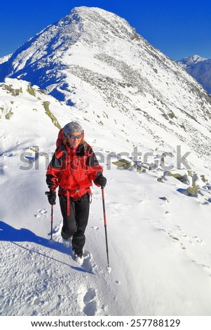 Sunny mountain ridge with snow and woman walking on snowy trail