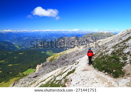 Sunny mountain slope and distant hiker on rocky trail in nice day of summer, Catinaccio massif, Dolomite Alps, Italy - stock photo