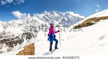 Sunny mountain slope covered with snow and woman climbing with trekking poles. Outdoor among peaks concept - stock photo