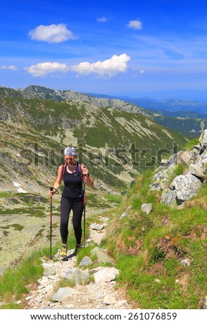 Sunny mountain trail and fit woman hiker - stock photo