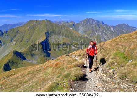 Sunny mountain trail and isolated backpacker walking along  - stock photo
