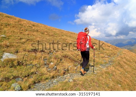 Sunny mountain trail with backpacker woman traversing grassy slope - stock photo