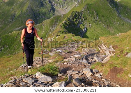 Sunny mountain trail with young woman hiker ascending with trekking poles - stock photo