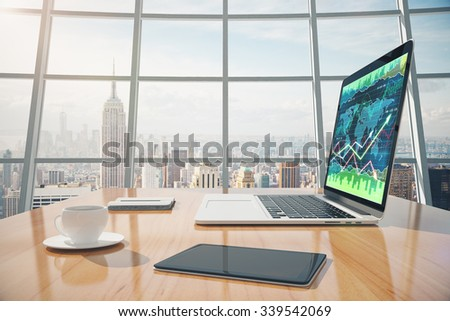 Sunny office with megapolis city view, digital tablet and laptop screen with business chart on the wooden table - stock photo