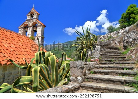 Sunny orthodox church and old stone stairs sided by Mediterranean vegetation, Montenegro - stock photo