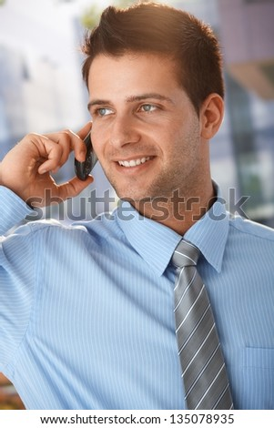 Sunny outdoor portrait of handsome businessman talking on mobile phone, smiling. - stock photo