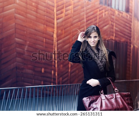 Sunny outdoor winter fashion portrait of young attractive woman holding a bag in the city. / This is a Vintage look photo. Some Color effects are added, a soft film noise and a custom white balance. - stock photo