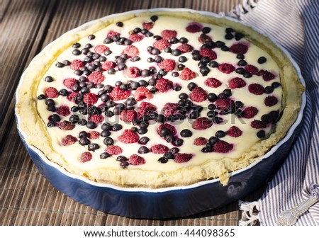 Sunny Photo with a morning breakfast in a rustic style. Cheesecake with raspberries and blueberries on wooden table. Selective focus picture - stock photo