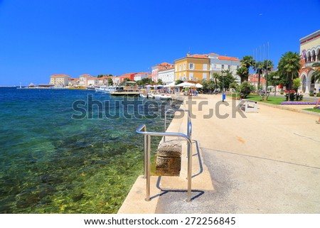 Sunny pier along Adriatic sea shore in traditional town and harbor, Porec, Croatia - stock photo