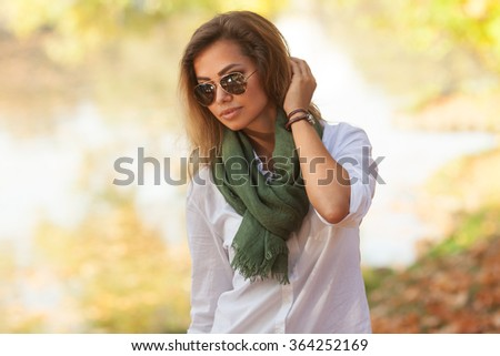 Sunny portrait of a beautiful young woman is sunglasses and in a green scarf - stock photo