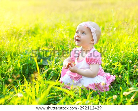 Sunny portrait of cute child on the grass in summer day - stock photo