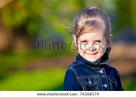 Sunny portrait of happy cute girl walking in a park - stock photo