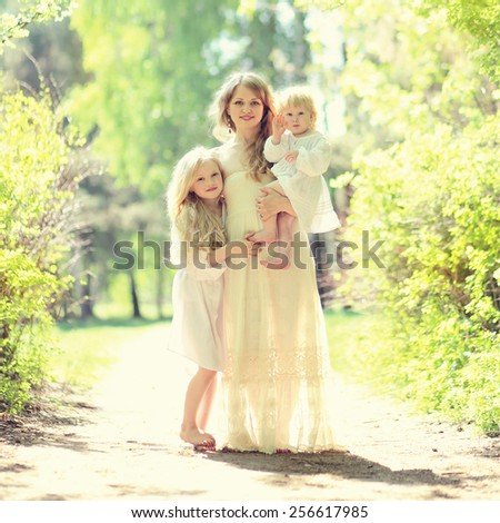 Sunny portrait of happy family on the nature, young mother hugging her two daughters in summer day - stock photo