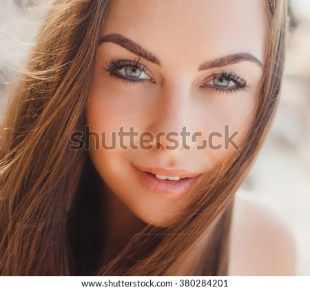 Sunny portrait of young beautiful woman brunette beautiful tanned skin, blue eyes, gorgeous hair, makeup, hairstyle, smiling with good humor summer vacation outdoor fashion style, close up,califorrnia - stock photo