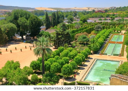 Sunny promenade and green pools in the gardens of the Alcazar of the Christian Monarchs (Alcazar de los Reyes Cristianos) Cordoba, Andalusia, Spain