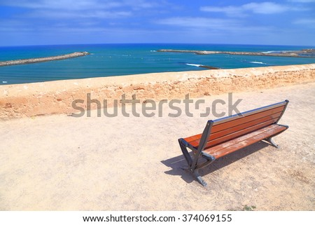 Sunny promenade and wooden bench above Bou Regreg river and Atlantic ocean, Kasbah of the Udayas, Rabat, Morocco - stock photo