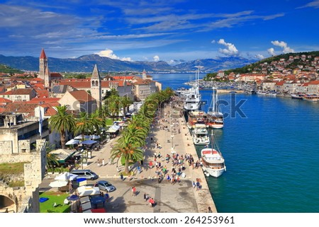 Sunny promenade of the old harbor and town of Trogir, Croatia - stock photo