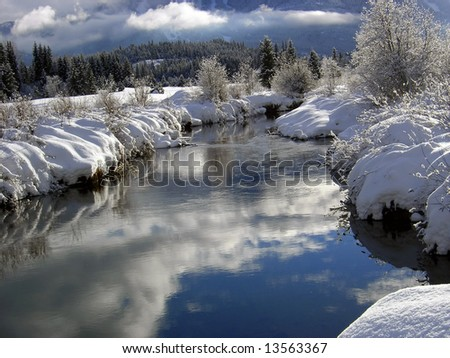 Sunny Riverbank after a snowstorm with reflecting water - stock photo
