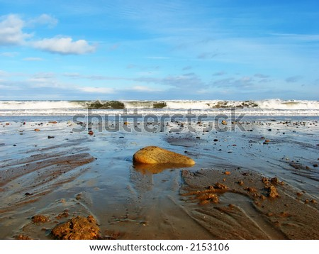 Sunny scenic focused on stone in foreground with tide in background