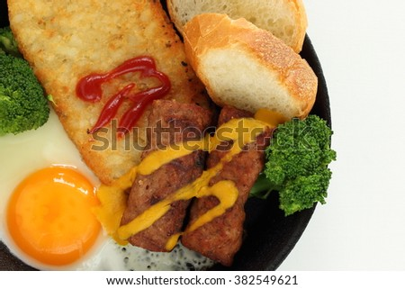 sunny side up egg and sausage fried on cast iron skillet for breakfast image