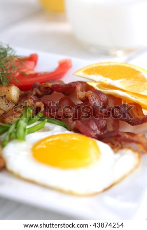Sunny side up eggs and bacon with fruit and tomato - stock photo