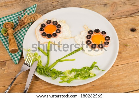 Sunny side up eggs decorated with vegetables, kid food - stock photo