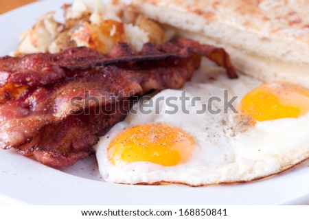 sunny side up eggs with hash browns and ciabatta toast - stock photo