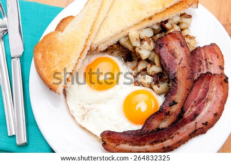 sunny side up eggs with organic bacon, hashbrowns and crsipy  toast - stock photo