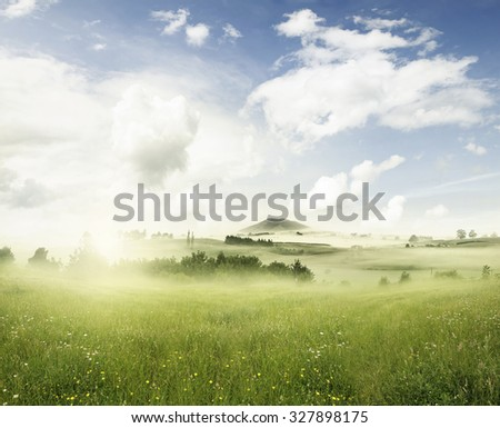 Sunny spring meadow in landscape - stock photo