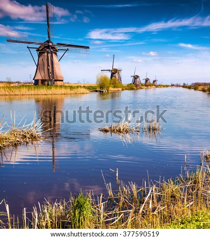 Sunny spring morning on the canal in Netherlands. Dutch windmills at Kinderdijk, an UNESCO world heritage site. - stock photo