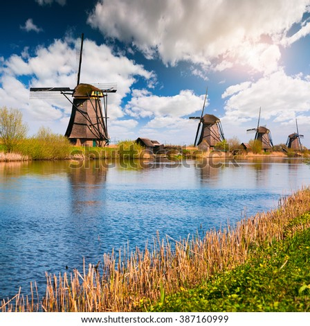 Sunny spring scene in the canal in Netherlands. Dutch windmills at Kinderdijk, an UNESCO world heritage site. Morning in Holland. - stock photo