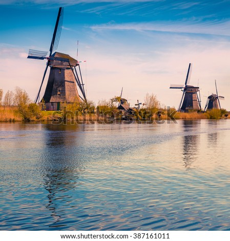 Sunny spring scene in the canal in Netherlands. Dutch windmills at Kinderdijk, an UNESCO world heritage site. Tipical Holland landscape. - stock photo