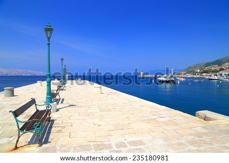 Sunny stone pier with street lamps and bench by the Adriatic sea, Senj, Croatia - stock photo