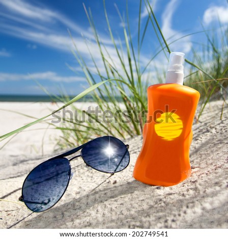 sunny summer beach with sunscreen and sunglasses for sun protection  - stock photo